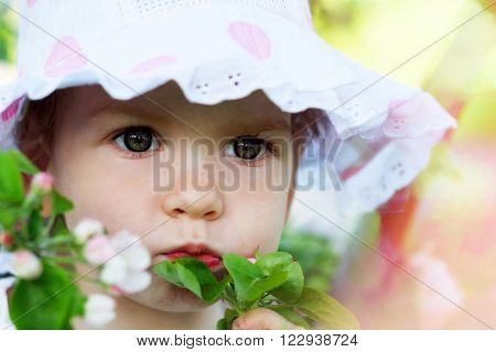 Beautiful girl in hat close up among the flowers