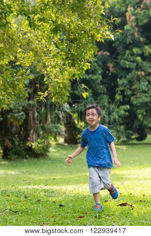 Portrait of little Asian boy running in the park
