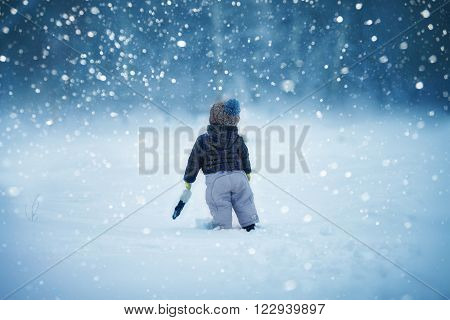 the kid walks in the winter snow