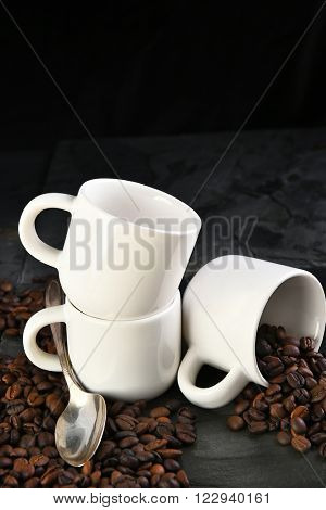 Closeup of coffee cups and coffee beans on a black slate background with copy space. Vertical format.
