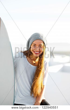 Portrait of a young smiling woman in white t-shirt and hat with surfboard on the white city background. Concept of a surfing as a lifestyle