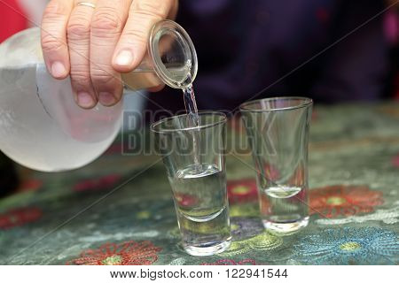 Person pouring vodka into glasses in the restaurant