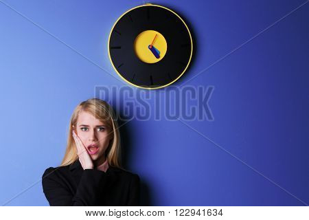 Young attractive woman under the clock, on blue background