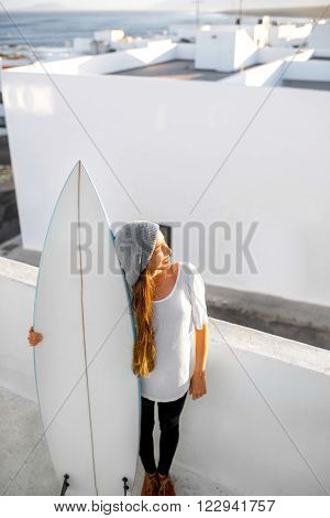 Young smiling woman in white t-shirt and hat standing with surfboard on the roof top on the white city background. Enjoying morning sunlight and preparing for surfing
