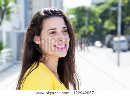 Caucasian woman in yellow shirt in the city looking sideways