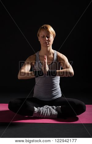 Young woman practicing yoga, Padmasana / Half Lotus Position