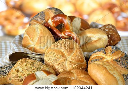 Various fresh Bavarian rolls and pretzels from the domestic master baker on a checkered tea towel; many blurry bakery goods in the background