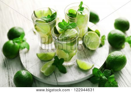 Fresh mojito drinks with lime, lemon and mint on wooden table