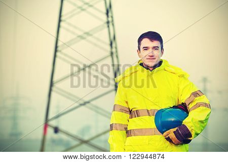 Worker wearing reflective clothing with helmet in hand
