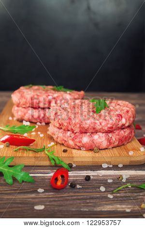 Raw ground beef burgers with chili pepper and arugula on rustic wooden table. Selective focus.