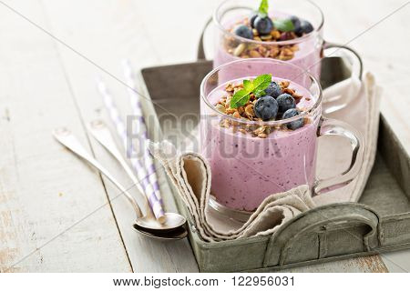 Blueberry smoothie with granola and fresh berries in glass mugs