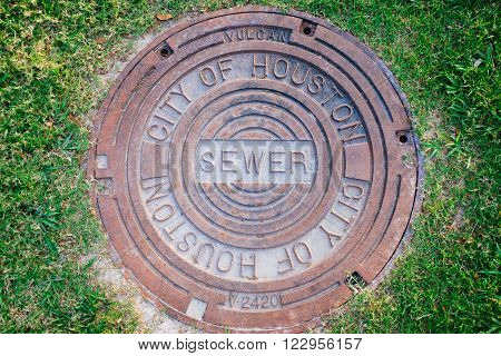 Manhole sewer cover of City of Houston in a park with green grass around