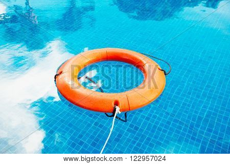 Life buoy afloat in a pool with blue clear water ** Note: Visible grain at 100%, best at smaller sizes