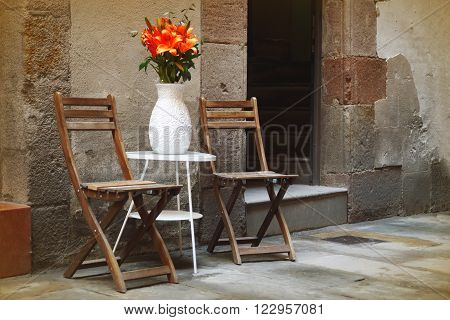 Rustic wooden chairs in the middle of a street in Barcelona, Spain. Peaceful romantic nook.