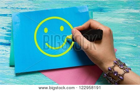 smiley women's hand drawing on a blue sheet with a yellow marker. the concept of happiness good mood can be used for ads postcards