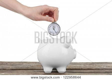 Piggy bank and a hand holding timer above it on white background