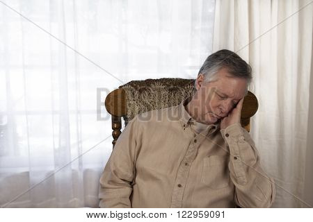 Older man suffering from the symptoms of fatigue. Sitting in a rocking chair at home.