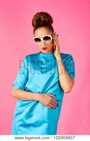 portrait on young beautiful woman in blue silk dress and white sunglasses ot the pink background