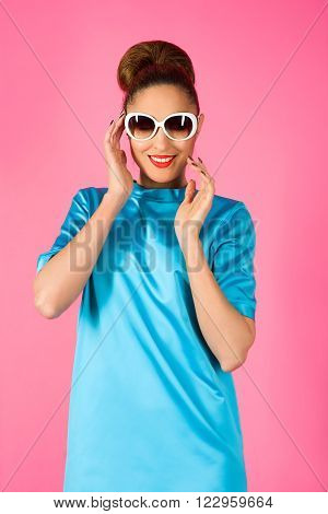 portrait on young smiling beautiful woman in blue silk dress and white sunglasses ot the pink background