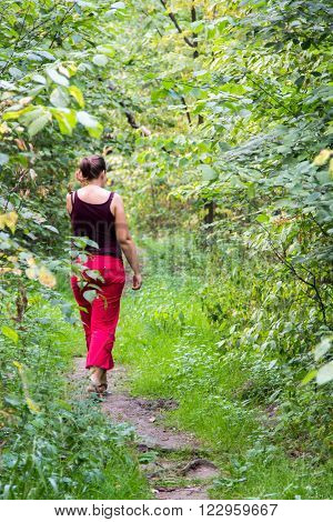 woman walking along a footpath in a dense forest