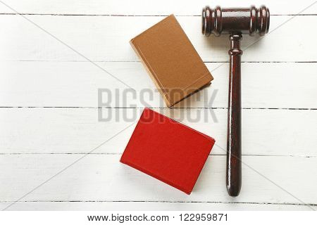 Gavel and books on wooden background