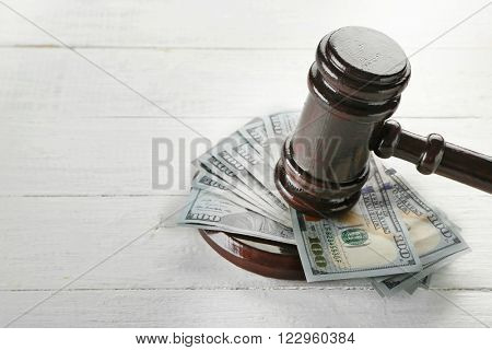 Gavel with money on wooden background