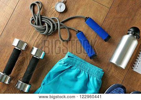 Athlete's set with female clothing, equipment and bottle of water on wooden background