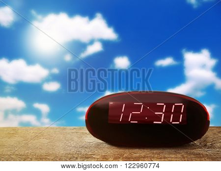 Digital clock showing 12:30 o'clock on wooden table,  blue sky background