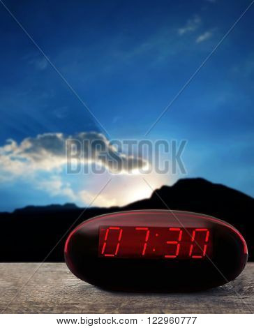 Digital clock showing 7:30 o'clock on wooden table, night background