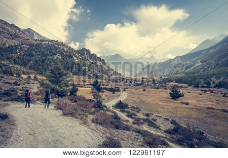 Pair of trekkers walking towards a village. Annapurna circuit in Nepal.