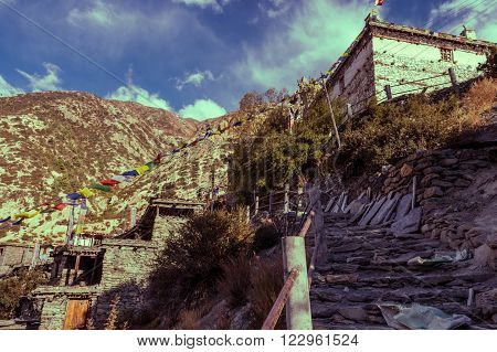 Stone staircase ascending towards traditional building. Braga village in Annapurna region.