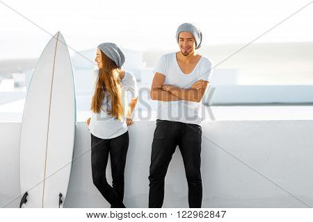 Young couple dressed alike in white t-shirts and hats enjoying summer vacations with surfboard on the roof top in the morning