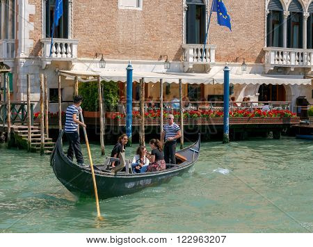 VENICE, Italy - 25 May, 2015: gondoliers transporting tourists in a gondola across the Grand Canal. Water transport is the most popular means of transportation in Venice.