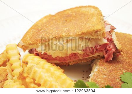 Close Up of a Ruben Sandwich Served with French Fries