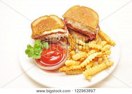 Ruben Sandwiches Served with French Fries on a White Plate