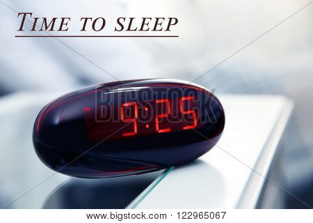 Digital clock showing 9:25 o'clock on a bedside table in bedroom
