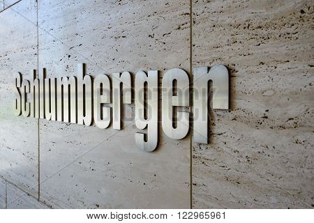HOUSTON, UNITED STATES - FEBRUARY 2016: Schlumberger - the biggest international oilfield service company sign made of polished metal on marble wall on February 2016 in Houston, United States.