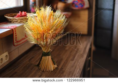 sheaf tied with a ribbon on a table by the window in a rustic interior. Yellow ears of wheat oats rye. soft focus.