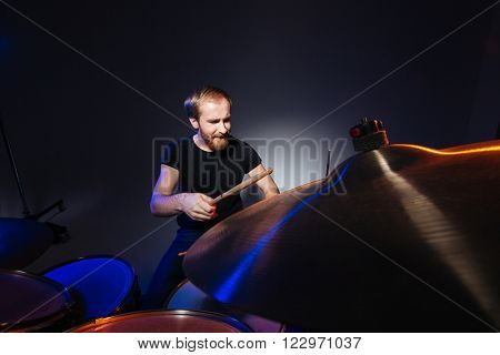 Serious bearded man drummer playing on his kit over dark background