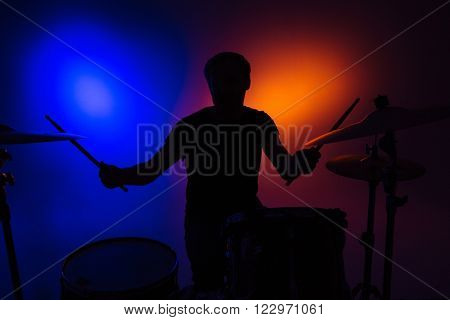 Silhouette of man drummer sitting and playing drums with sticks over colorful backgound