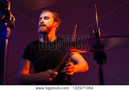 Portrait of focused handsme bearded drummer playing drums over dark background