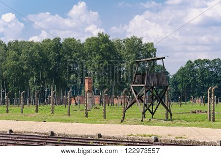 Auschwitz II - Birkenau, unloading ramp in the foreground with a watch tower and Sector II in the background behind the fence and sewage plant further back