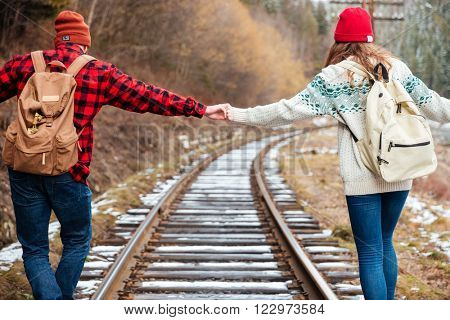 Beautiful young couple with backpacks holding hands and walking along railroad together