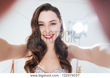 Happy charming woman making selfie photo