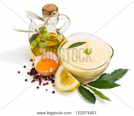 Mayonnaise with products for making mayonnaise olive oil egg yolk lemon spices) isolated on a white background.