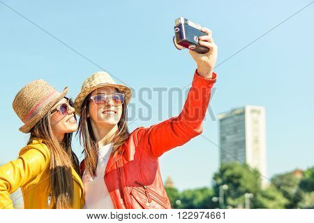 Young hipster friends make selfie photo with old retro camera in Italy while traveling across Europe on vacation - Funny outdoor activity of young fashion students away from home -