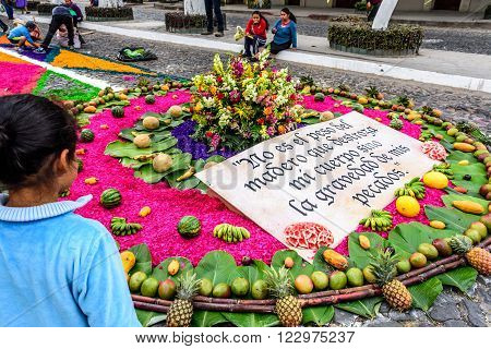 Antigua Guatemala - March 20 2016: Girl admires handmade Palm Sunday carpet for procession in town with most famous Holy Week celebrations in Latin America. Sign reads