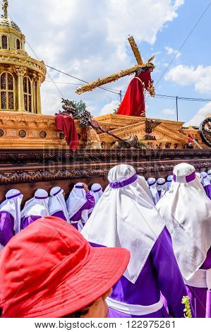 Antigua Guatemala - March 20 2016: Float bearers called cucuruchos carry float with Jesus in Palm Sunday procession in colonial town with most famous Holy Week celebrations in Latin America.