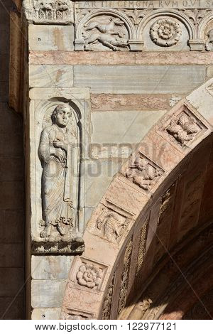 Detail from Verona Cathedral old romanesque porch with relief of John the Evangelist and medieval animals and monsters