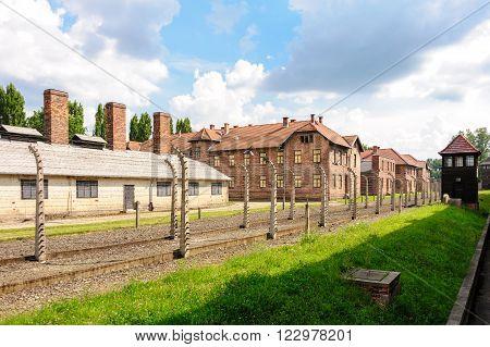 OSWIECIM, POLAND - JULY 3, 2009: Auschwitz I - Birkenau, rear view of kitchen, Block 25, fence and watch tower